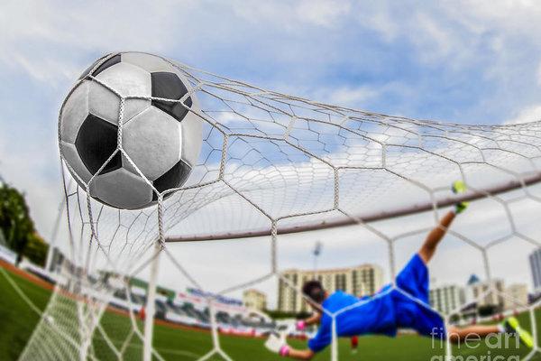 soccer ball in goal  by Anek Suwannaphoom
