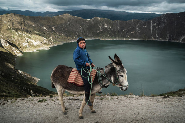 A young indigenous boy with his donkey at Quilotoa Lake in Ecuador by Kamran Ali